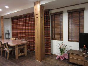 エスニック調のカーテンと木製ブラインドの組み合わせ